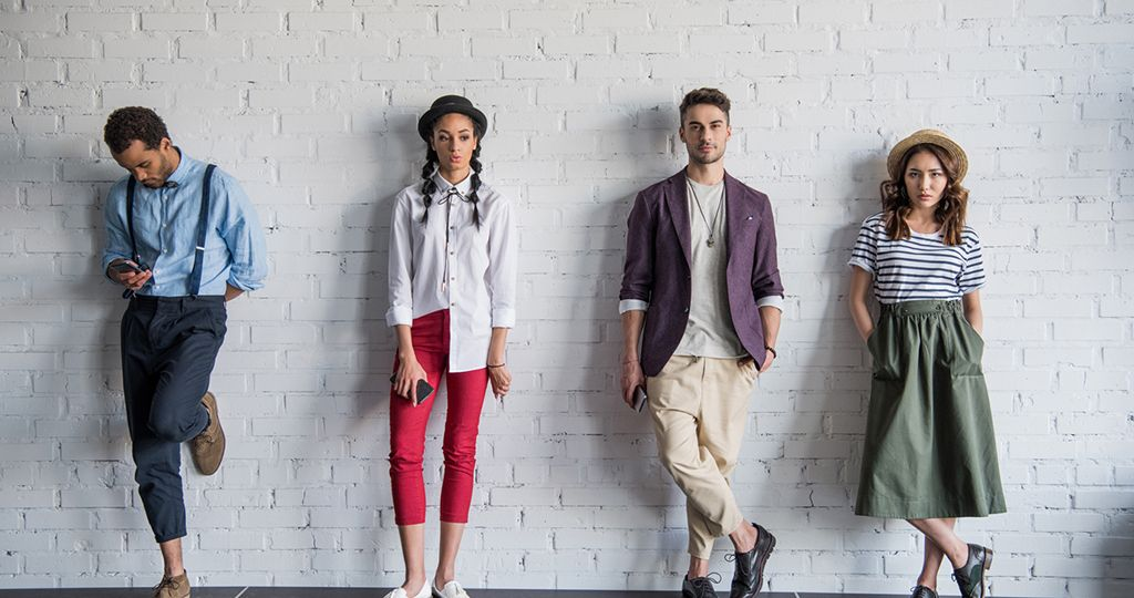 young multiethnic friends posing in stylish clothes near brick wall