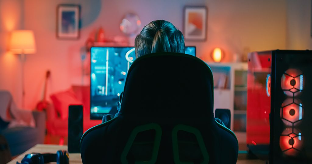 Back Shot of a Gamer Playing in First-Person Shooter Online Video Game on His Powerful Personal Computer. Room and PC have Colorful Neon Led Lights. Cozy Evening at Home.